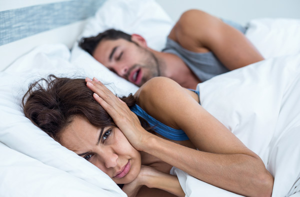 Woman covering ears while husband snores